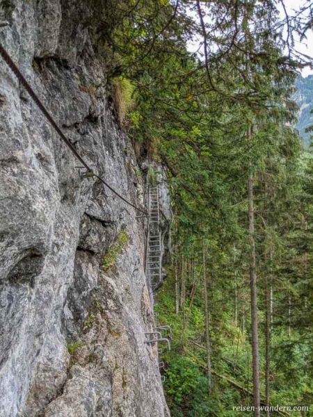 Leiterin und Eisenkramppen an Felswand des Schmied-Klettersteig
