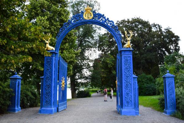 ein blaues Tor mit goldenen Figuren stellt den Eingang zum Park da