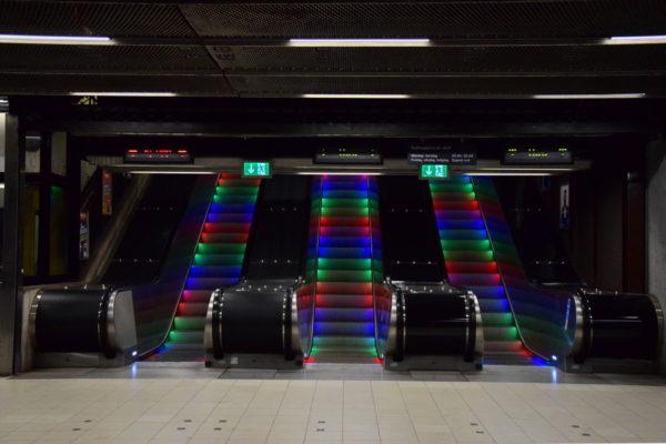 Eine Rolltreppe wird mit bunten Lichtern bestrahlt