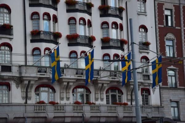 An einer Fassade hängen 4 schwedischee Flaggen