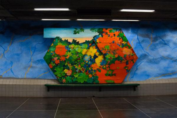 Vor einer blauen Höhlenwand steht eine Bank, welche mit gemalten Blumen verziert ist