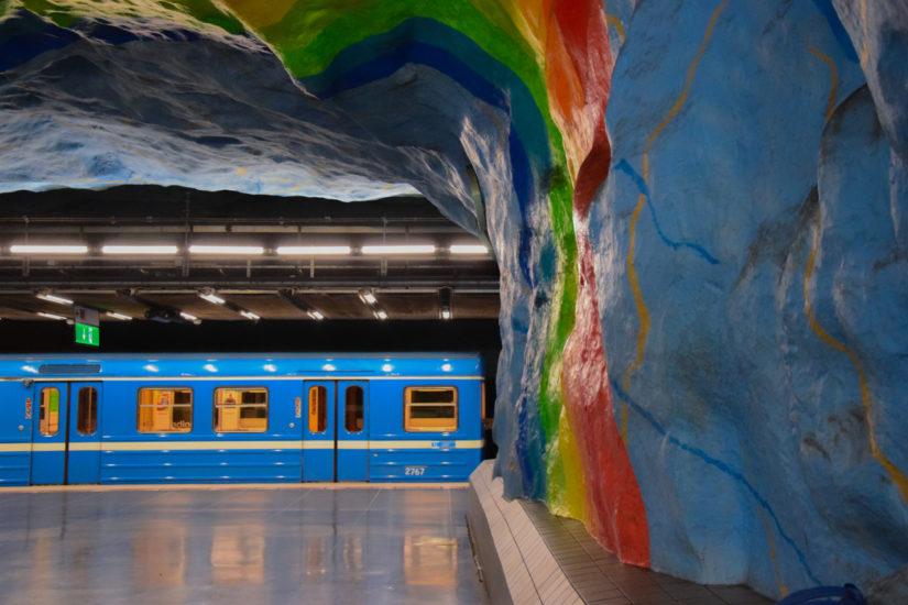 Eine U-Bahn fährt in eine Station ein, welche mit einem Regenbogen gestaltet ist