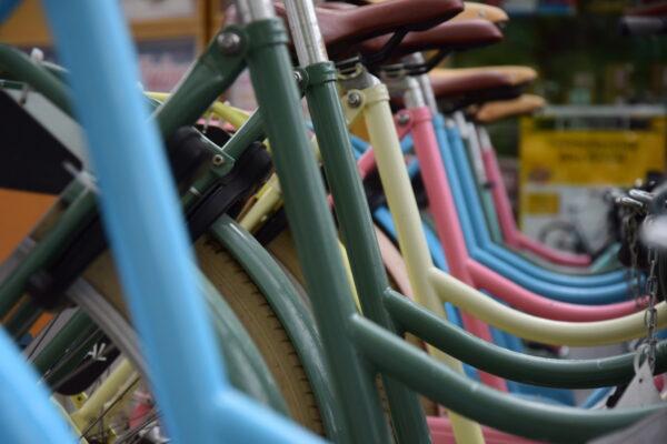 Eine Reihe bunte Fahrräder steht am Straßenrand