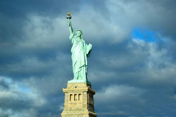 Die Freiheitsstatue steht vor einem blauen Himmel