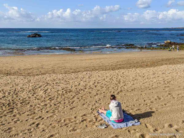 Frau sitzend auf einem Badehandtuch am Srand Playa Las Canteras