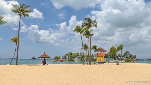Strand mit Rettungsschwimmerturm und Palmen auf Sentosa