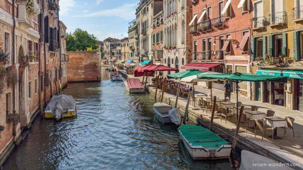 Boote in und Cafes an einem Kanal in Venedig