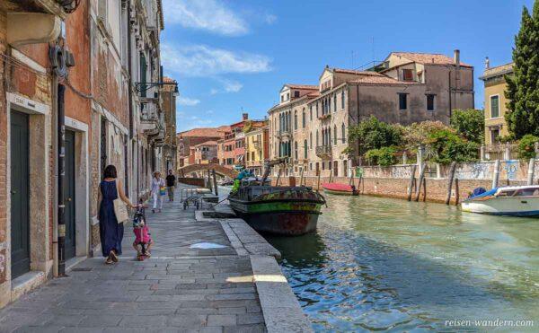 Kanal mit Boot und Frau mit Kind in Venedig