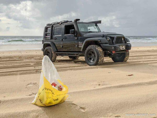 Müllbeutel mit Geländewagen am Strand
