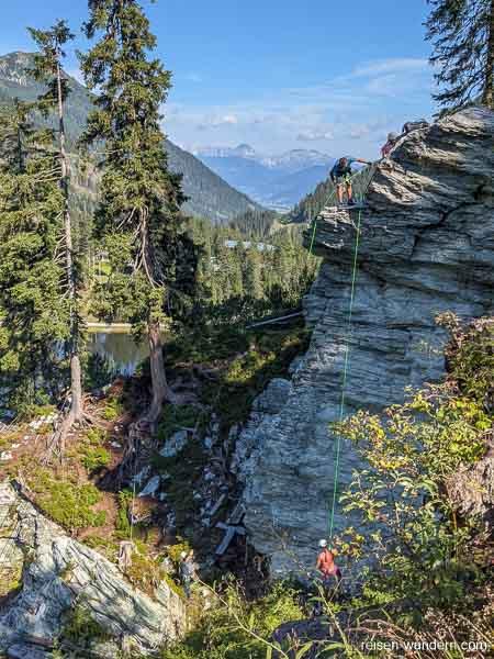 Abseilen an der Felswand bem Klettersteig